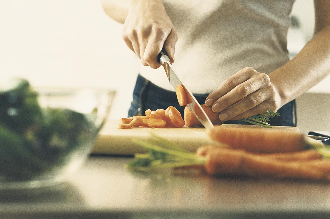 Frau beim Schneiden von Karotten. Thema: Herzgesunde Ernährung