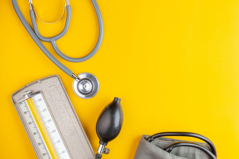 Stethoskop und Blutdruckmessgerät vor gelbem Hintergrund