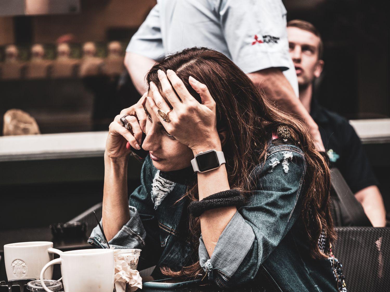 Gestresst aussehende Frau im Café am Telefon. Thema: Herzinfarkt-Risiko