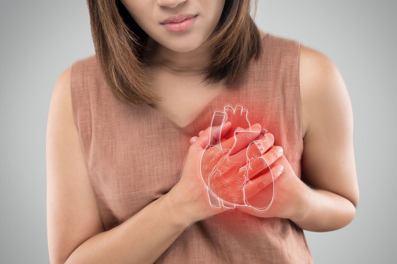 Eine Frau hält sich die Hände an die Brust, weil ihr Herz schmerzt.