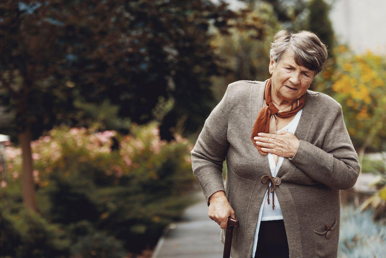 Eine ältere Dame, die beim Gehen Probleme mit dem Herzen hat.