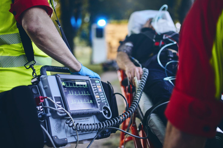 Eine Person wird von Rettungssanitätern abgeholt, ein EKG ist angeschlossen und zeigt die Herzfrequenz.