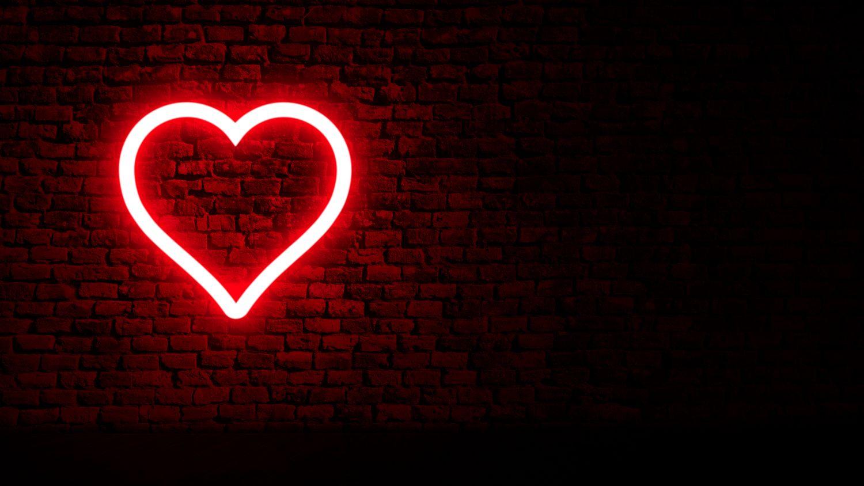 Ein Leuchtherz vor einer Backsteinwand. Thema: Kardiovaskuläre Erkrankung