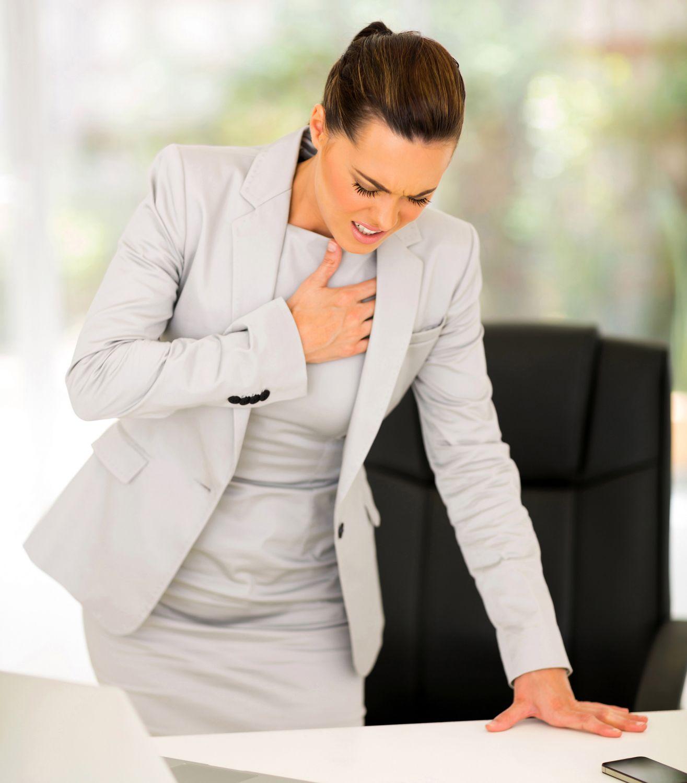 Geschäftsfrau erleidet eine Herzattacke im Büro.