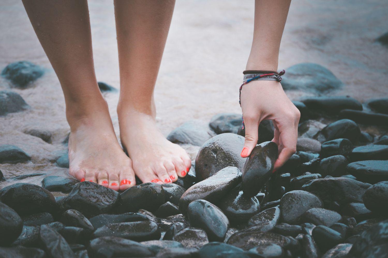Flussbett, in dem jemand einen Stein aufhebt. Thema: Blutkreislauf und Gefäßtherapie