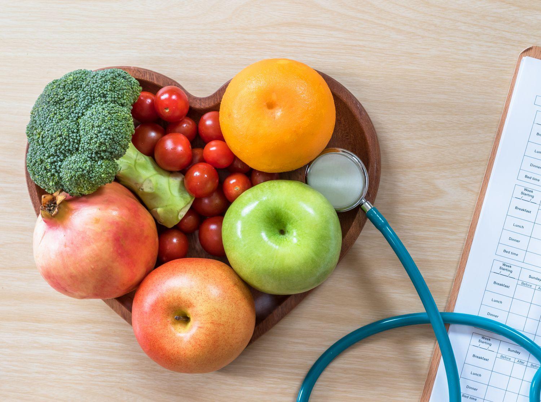 Obst und Gemüse zu einem Herz angeordnet, neben einem Stethoskop.