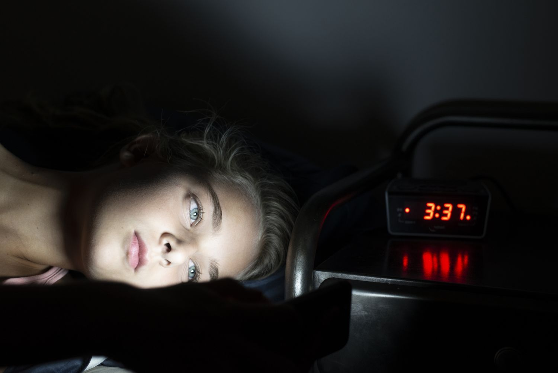 Mädchen liegt wach im Bett und schaut aufs Smartphone.