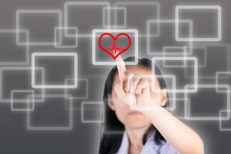 Frau tippt Herz im virtuellen Bildschirm an. Thema: Herzmedizin