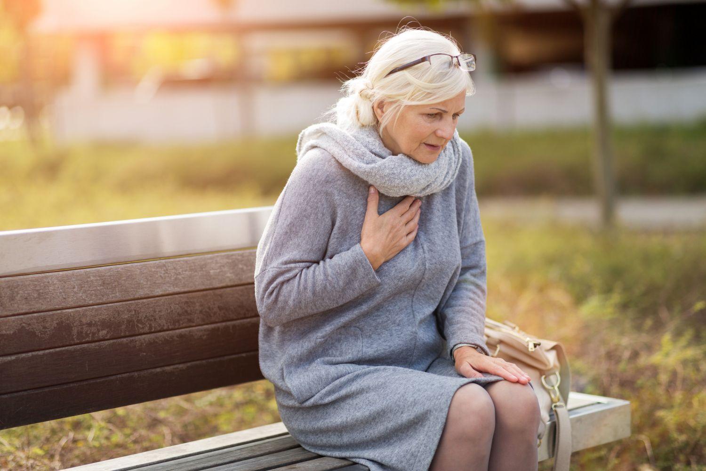 Ältere Frau sitzt auf einer Parkbank und fässt sich ans Herz. Thema: Krebsnachsorge