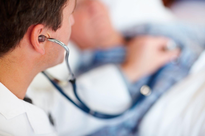 Arzt hört Patienten mit Stethoskop ab. Thema: Medizintechnologien
