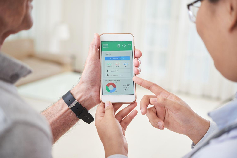 Arzt und Patient schauen auf ein Smartphone und besprechen die Daten, die dort angezeigt werden